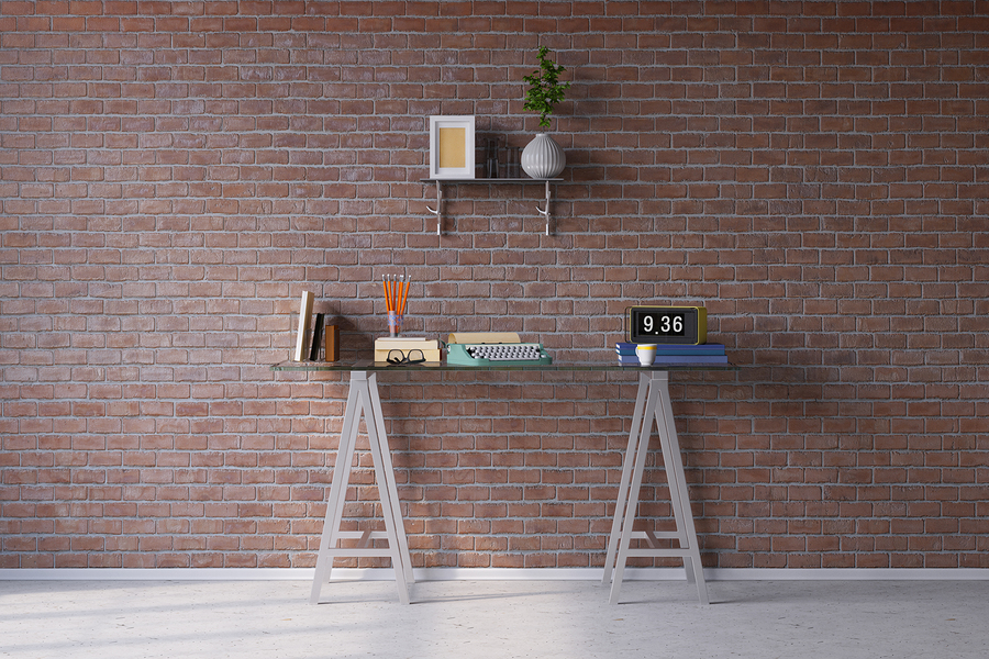 Retro desk with typewriter in vintage look in front of a brick w